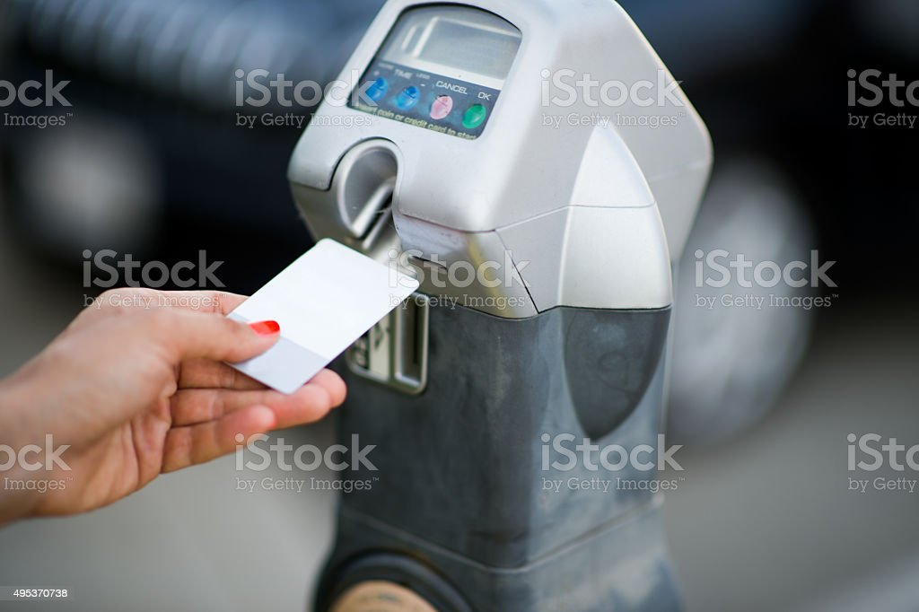 Female hand inserting card into parking meter stock photo
