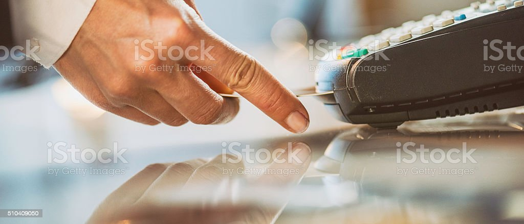 Female hand inserting credit card into a reader stock photo