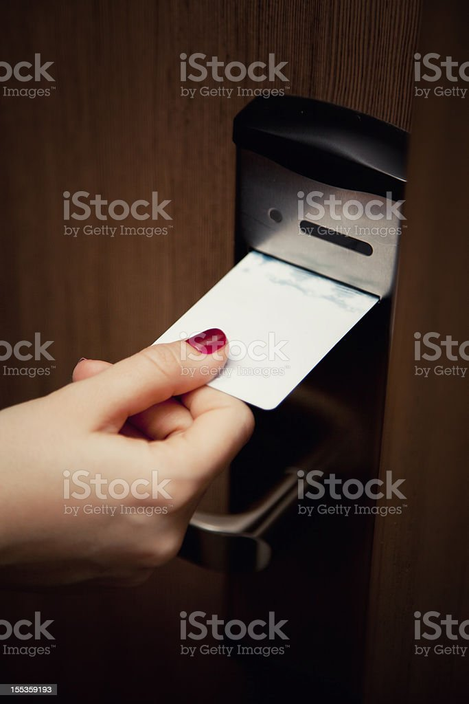 Female Hand Inserting Key Card Into Hotel Room Door Lock stock photo