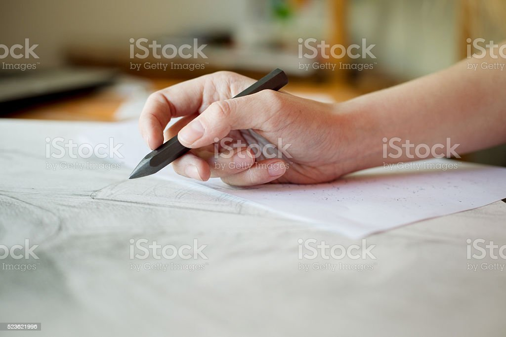Female hand is drawing with a pencil stock photo