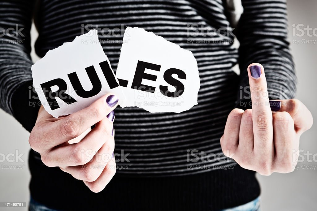 "Female hand makes obscene gesture while holding torn ""rules"" sign royalty-free stock photo"