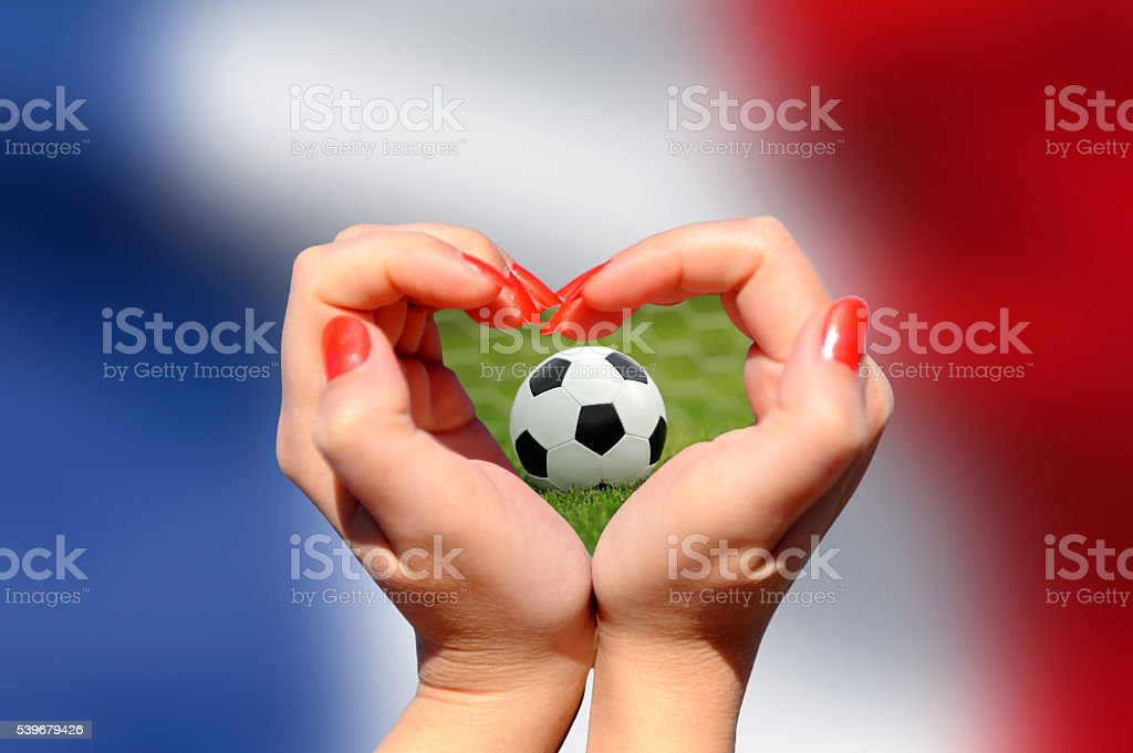 Female hand making a heart shape with soccer ball stock photo