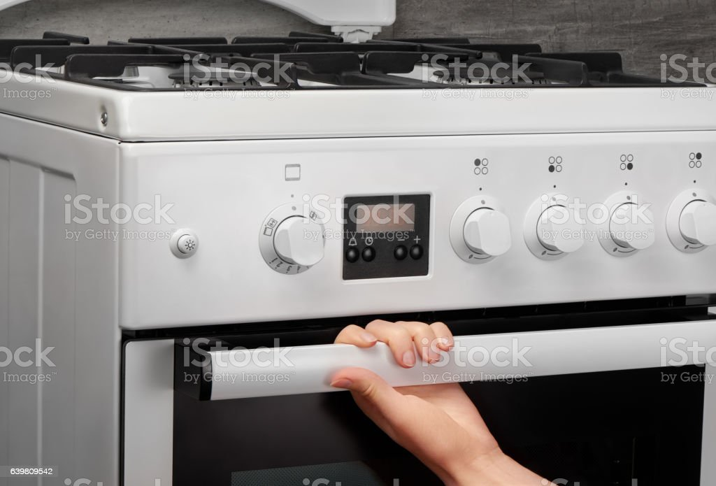 Female hand opening oven in white kitchen gas stove stock photo