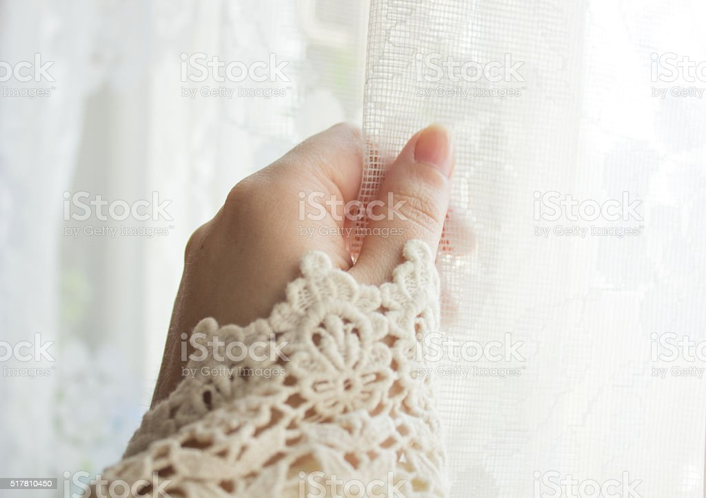 Female hand opening the curtain on the window stock photo
