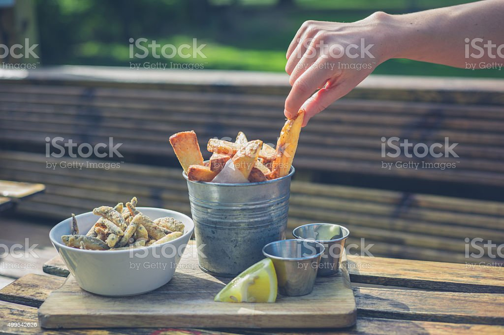 Female hand picking up chip from bucket stock photo