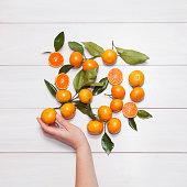 Female hand picks Tangerine (mandarin)