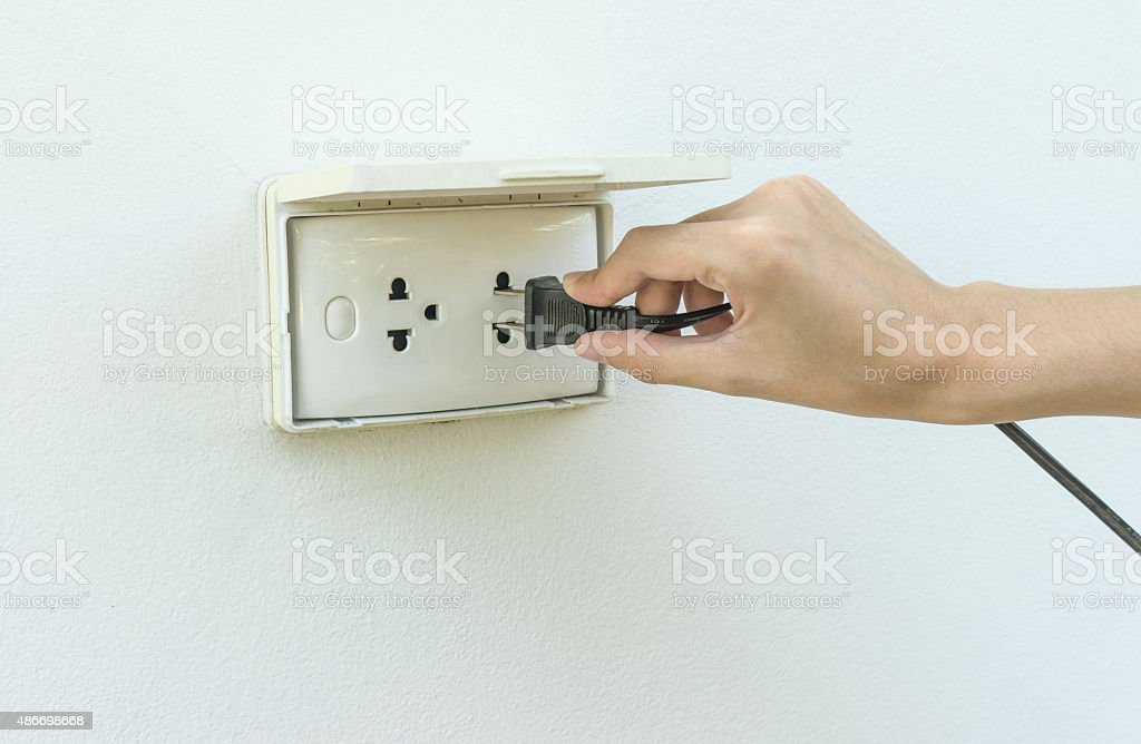 Female hand plugging in appliance to electrical outlet in wall stock photo