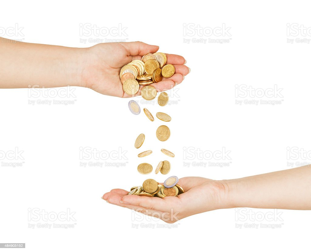 Female hand pour down coins into hands of another person. stock photo