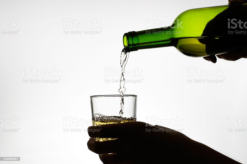 Female hand pouring wine into glass stock photo