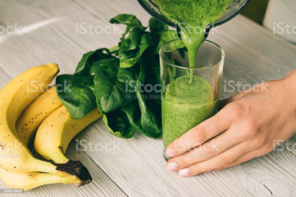 Female hand pours a smoothie of banana and spinach stock photo
