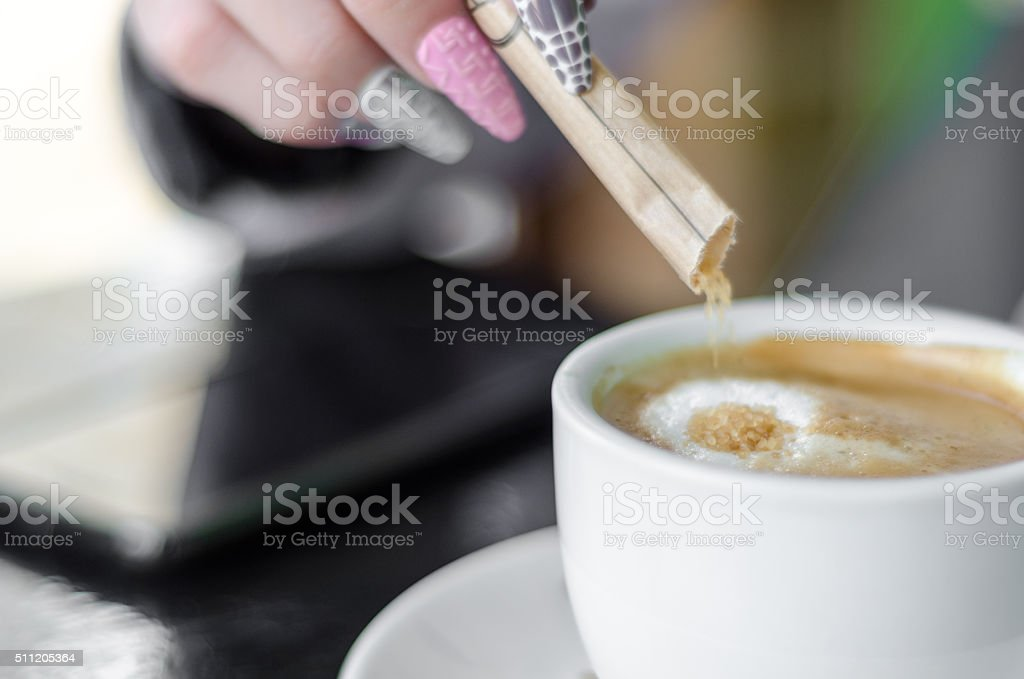 Female hand pours sugar into coffee stock photo