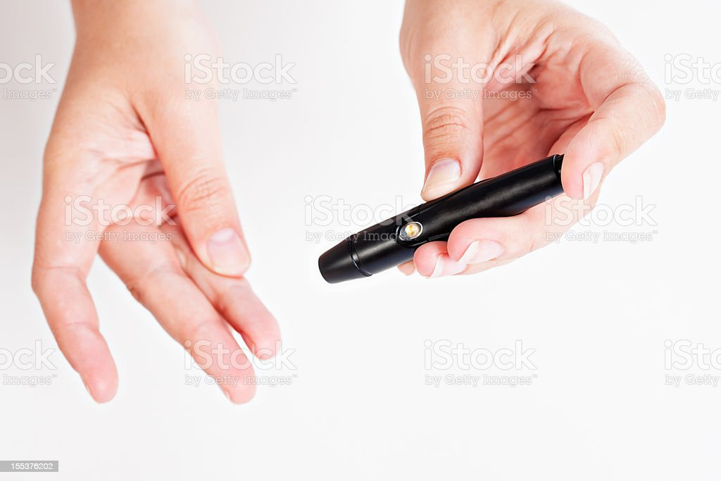 Female hand preparing to use automatic lancet for drawing  blood stock photo