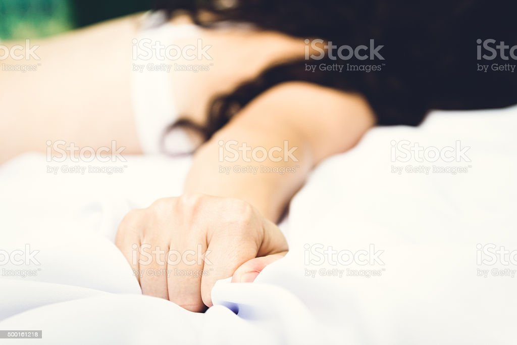 Female hand pulling white sheets in ecstasy stock photo