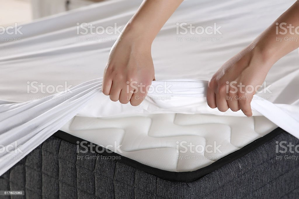 Female hand pulling white sheets stock photo
