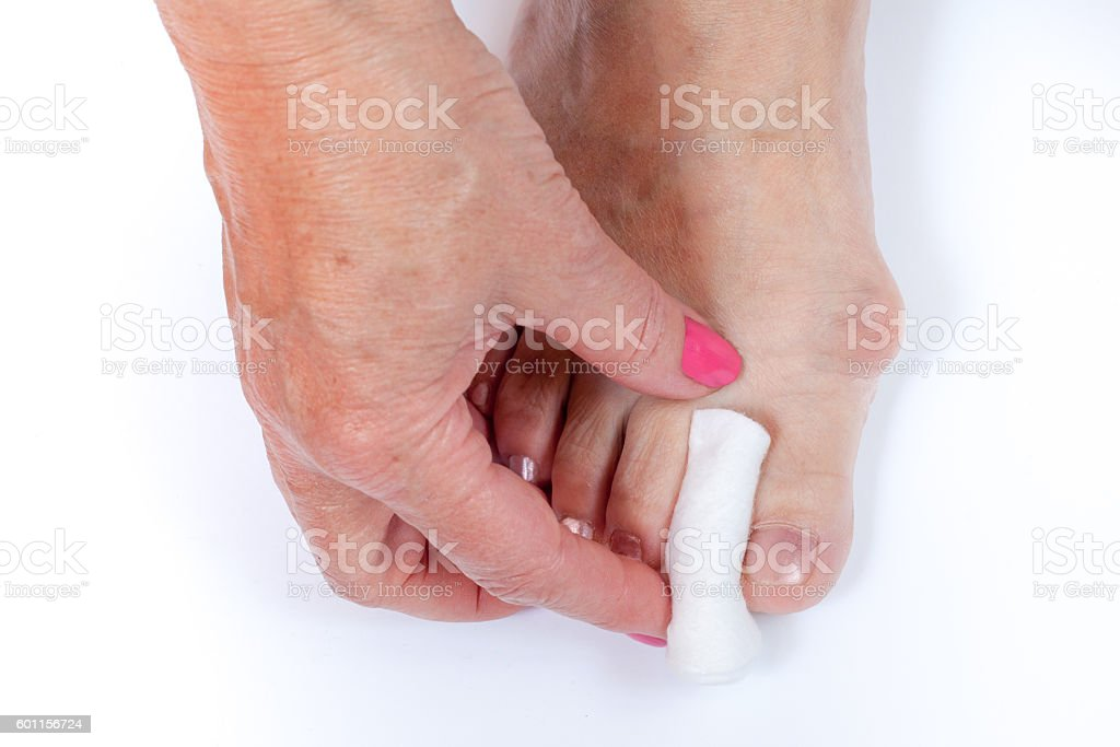 female hand put a buffer between the foot toes stock photo
