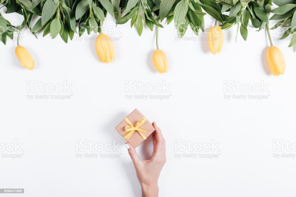 Female hand puts a box with gift on the table stock photo