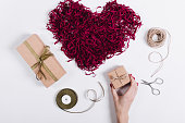Female hand puts boxes with gifts near a decorative heart