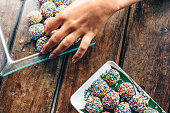 female hand putting brazilian brigadeiros to plate on wooden table