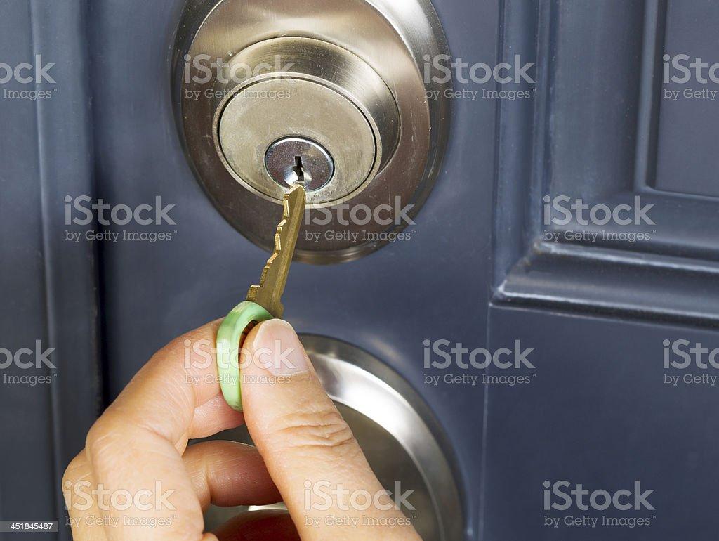 Female hand putting house key into door lock stock photo