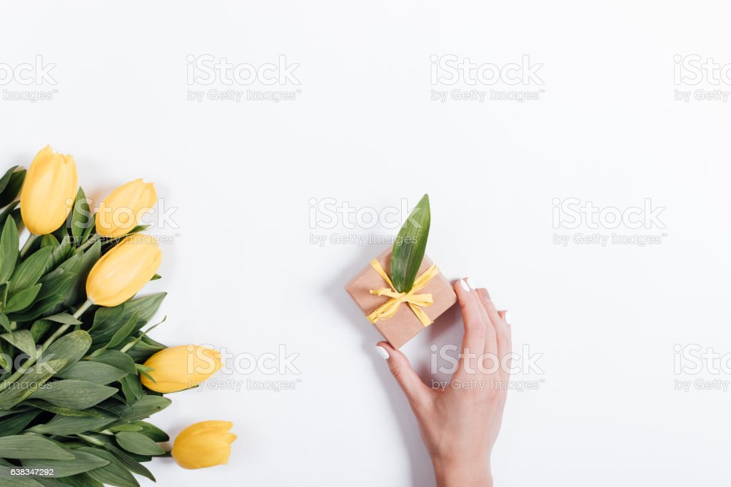 Female hand putting on the table a box with gift stock photo