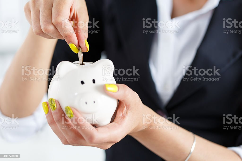 Female hand putting pin money coins stock photo