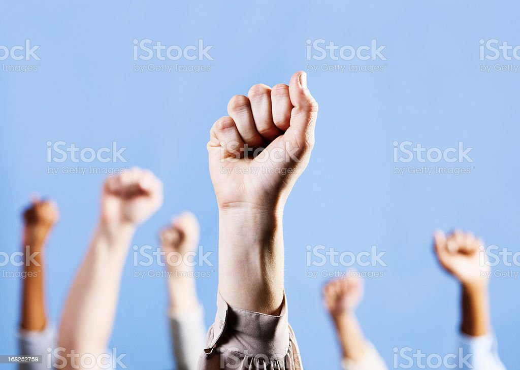 Female hand raises clenched fist of solidarity, others in background stock photo