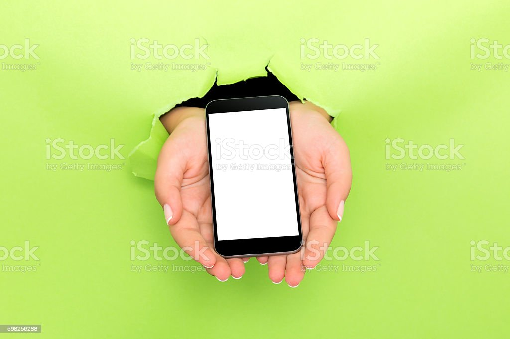 Female hand reaching through torn green paper sheet stock photo