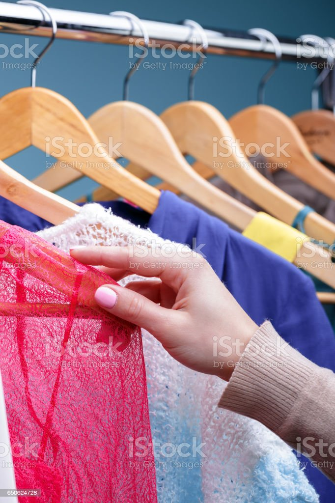 female hand selects colorful clothes on wood hangers on rack in stock photo