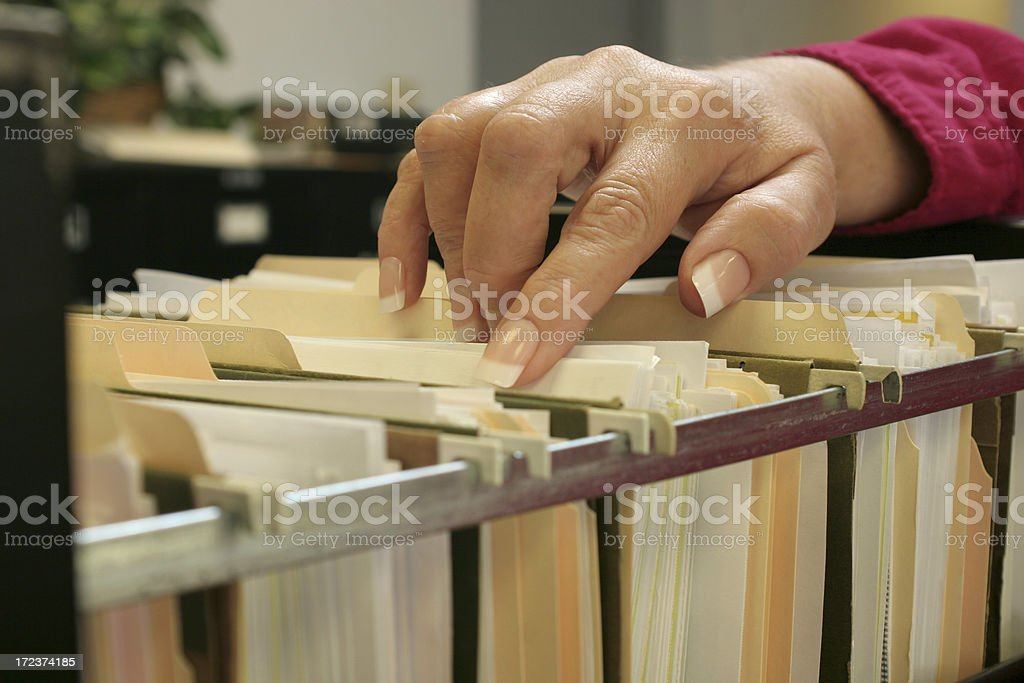 Female hand sorting through files stock photo