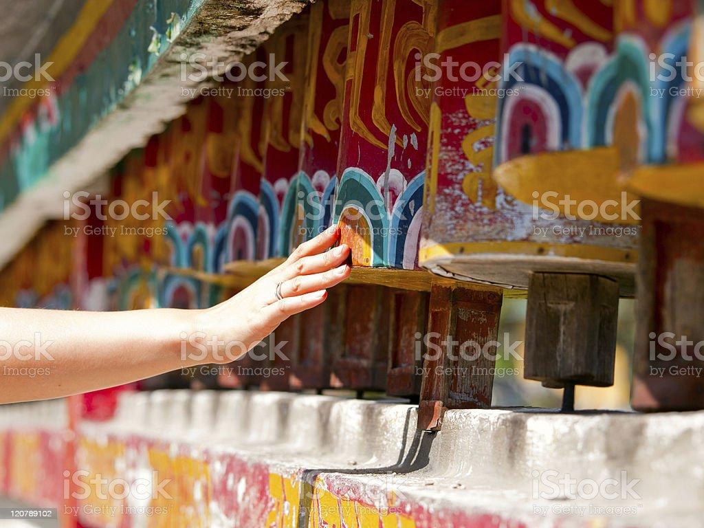 Female hand spinning the prayer wheels for good karma stock photo