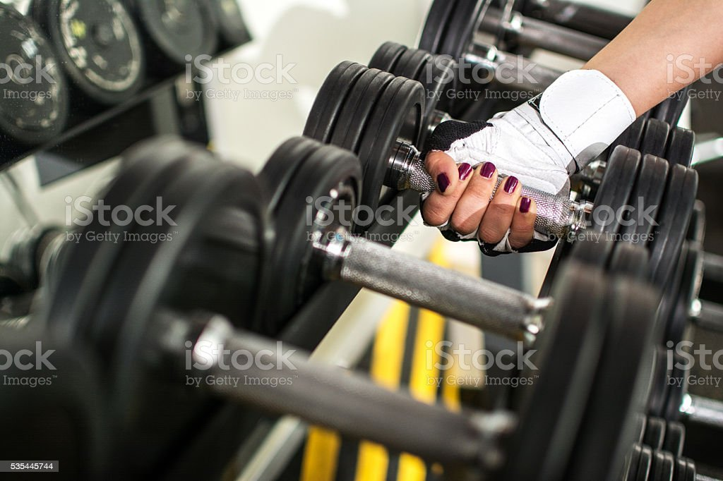 Female hand taking a dumbbell. stock photo
