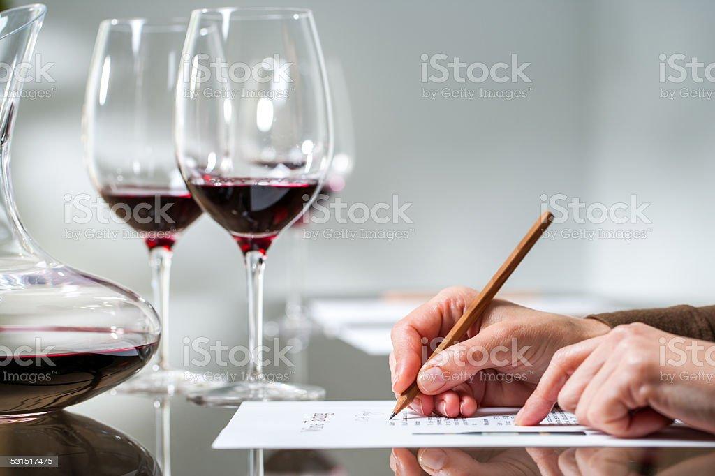 Femme main prendre des notes au red dégustation de vins. photo libre de droits