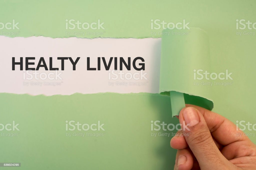 Female hand tearing the word Healty Living stock photo