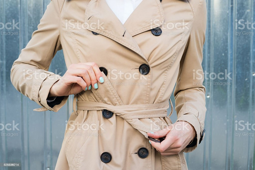 Female hand tie belt on a coat outdoors stock photo