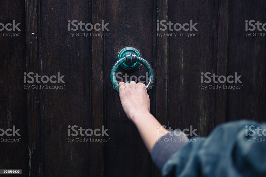 Female hand touching knocker stock photo