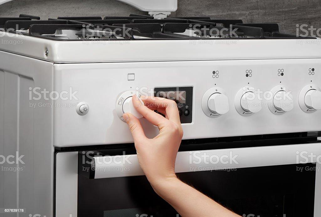 Female hand turning on white kitchen gas stove on gray stock photo