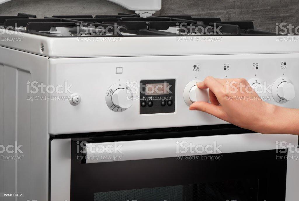 Female hand turning on white kitchen gas stove stock photo