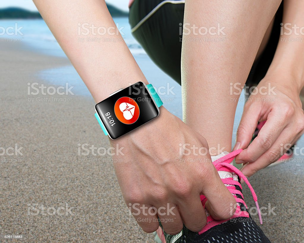 female hand tying shoelaces wearing bright green watchband touch stock photo