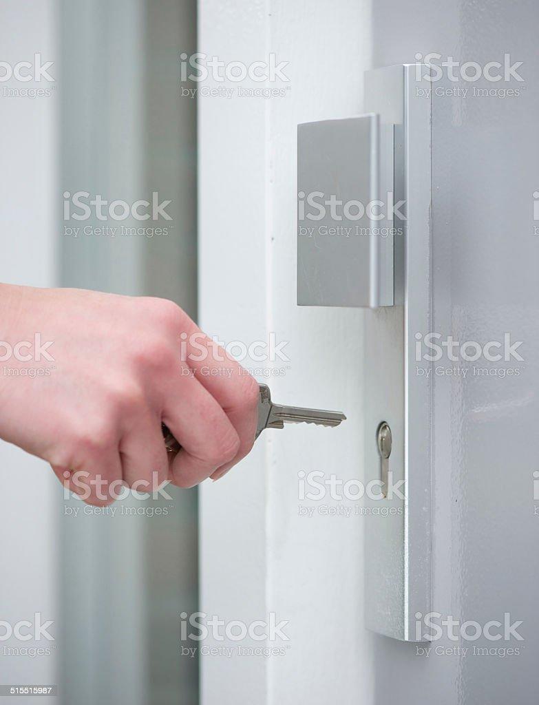 Female hand unlocking door lock stock photo