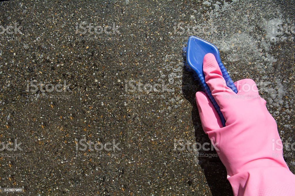 Female hand with kitchen glove cleans stone pavement stock photo