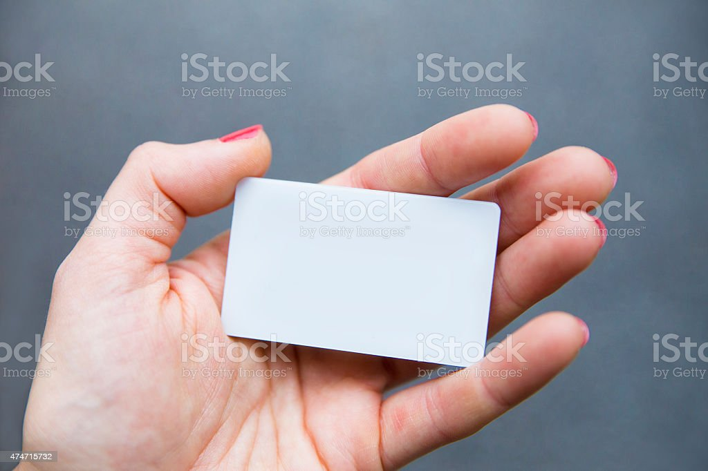 Female hand with pink nail polish holding small white card stock photo