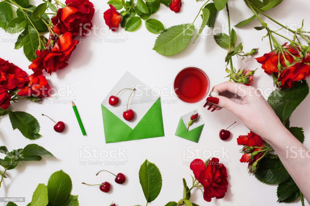 Female hand with red fingernails holding a cup of tea, red tea, ripe cherries, small envelopes, roses lay on a white background. Tea drinking during work. Healing drink. Berry compote. Flat lay stock photo
