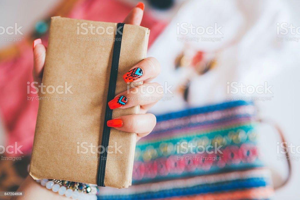Female hand with stylish colorful boho nails holding notes stock photo