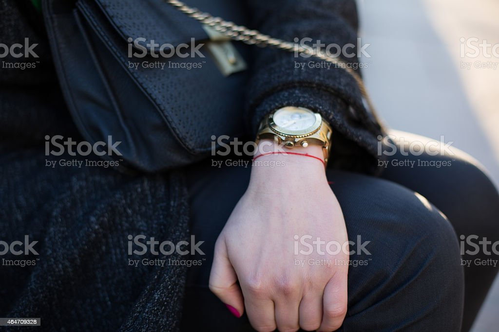 Female hand with the watch laying on the knees stock photo