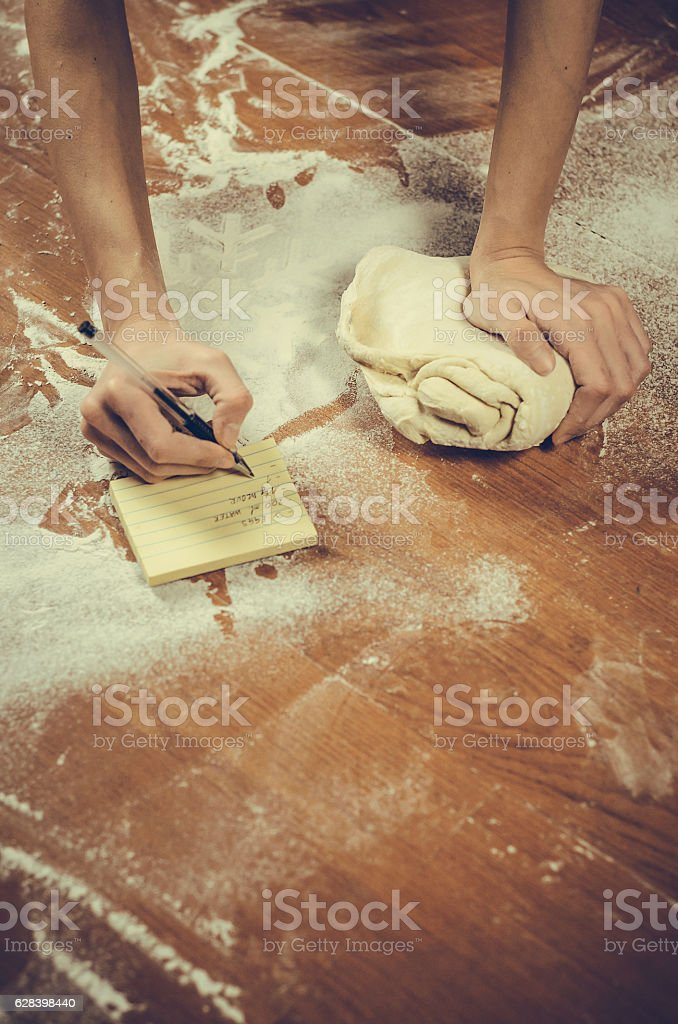 Female hand writes a recipe for pizza or donuts stock photo