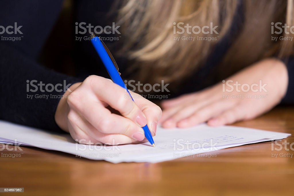 Female hand writing on paper stock photo