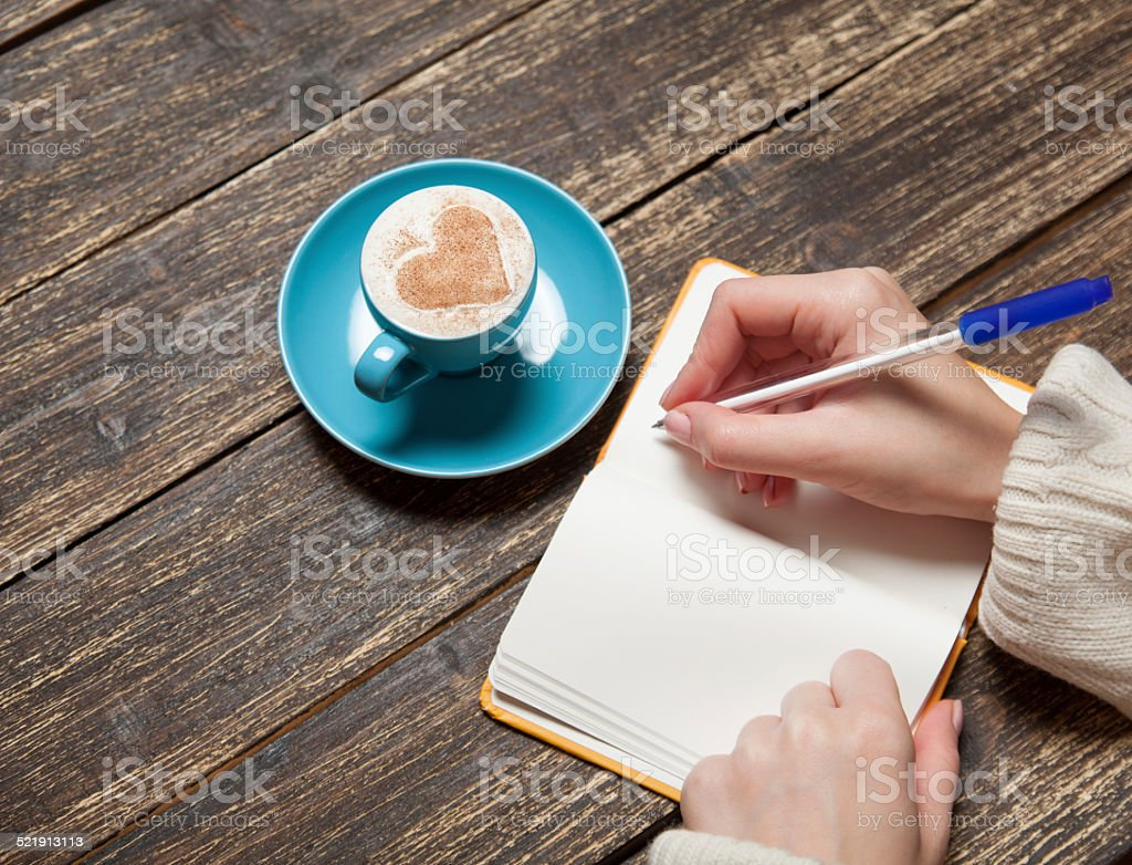 Female hand writing something in notebook near cup of coffee. stock photo