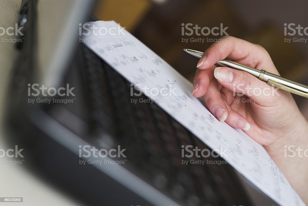 Female hand writing with pen on paper atop a laptop royalty-free stock photo