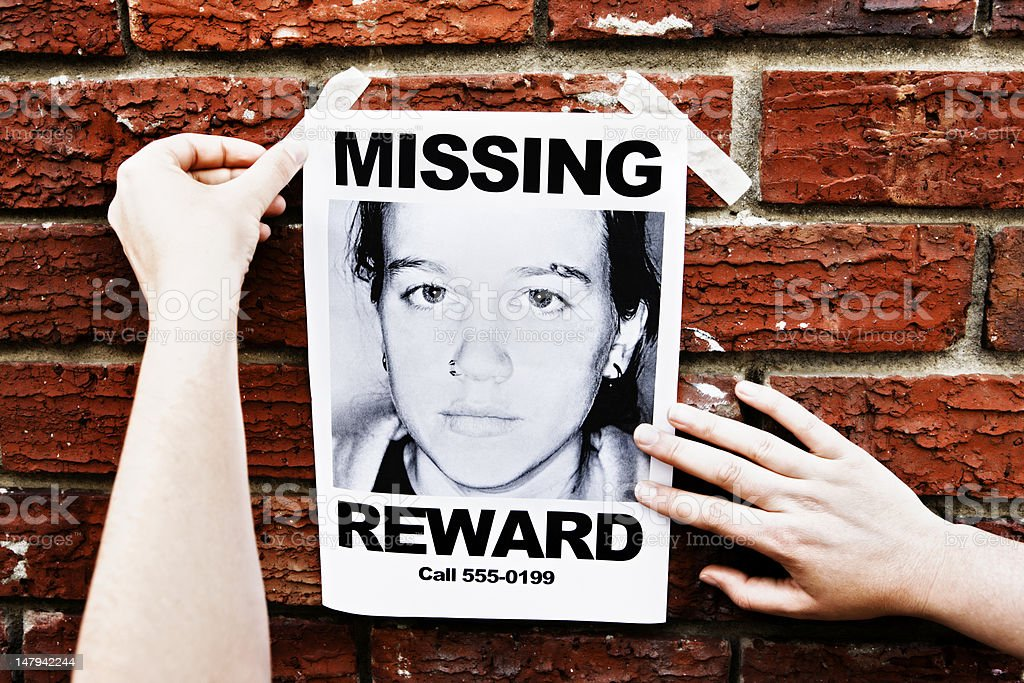 "Female hands attach ""Missing"" poster of teenage girl to wall royalty-free stock photo"