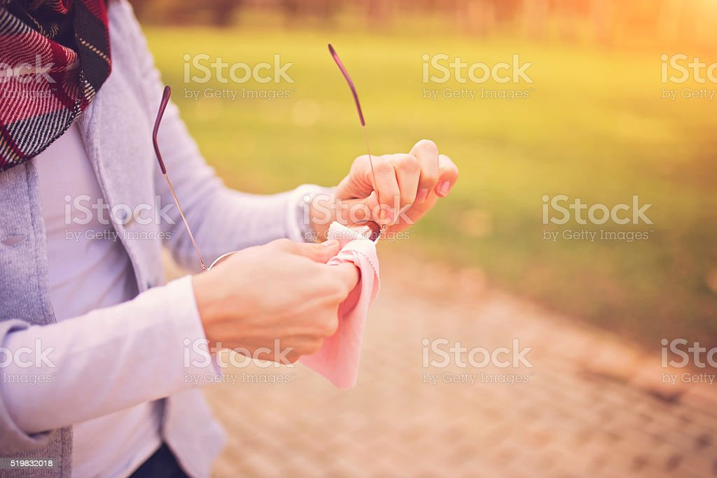 Female hands cleaning sunglasses in park stock photo
